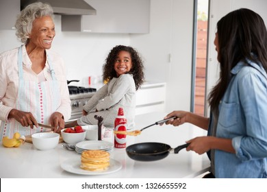Multi Generation Female Family In Kitchen At Home Making Pancakes Together