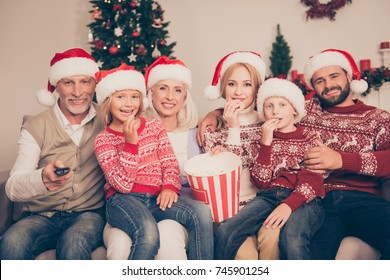 Multi generation, happiness, friendship. Group of cheerful relatives bonding on couch, excited, mom, dad, siblings, grandad, granny, in knitted cute traditional x mas costumes, firtree, home, movie