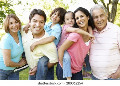 Multi Generation Hispanic Family Standing In Park