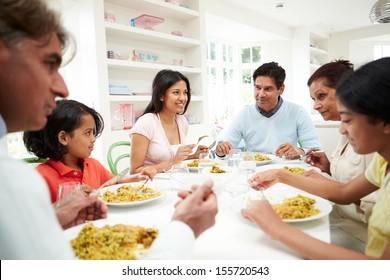 Multi Generation Indian Family Eating Meal At Home