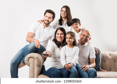 Multi generation Indian/asian family watching TV at home while sitting on sofa/couch, selective focus
