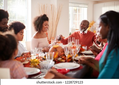 Multi generation mixed race family holding hands and saying grace before eating at their Thanksgiving dinner table, selective focus