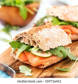 Multi grain ciabatta sandwich with smoked salmon, fresh cucumber and arugula salad leaves