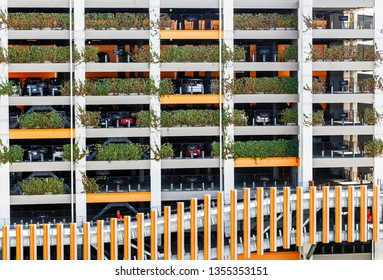 Multi level parking garage decorated with green plants with many cars parked, concept of eco world.