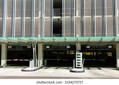 Multi level parking garage entrance and exit. Spaces available outdoor parking sign with LED counter indicating the number of open or empty parking spaces at garage levels.