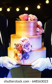 Multi level white wedding cake on a base and pink flowers on top.