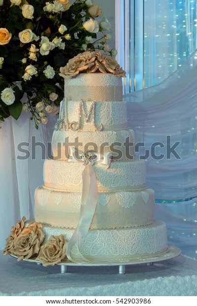 multi level white wedding cake on a silver base and gold flowers