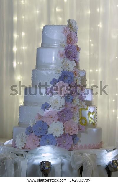 multi level white wedding cake with pink flowers.