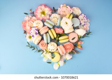 Multi сolored macaroons cakes with big and small different flower buds lay out in the shape of a heart on a blue background. Copy space. Bakery, cooking, gifts, conceptual and advertising.