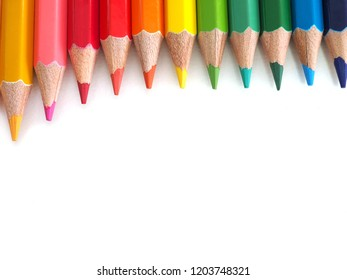 multi pencil colors row on white paper background with copy space . look like rainbow  . variety color can improve art or creativity skill of child student . well use at education class in school .