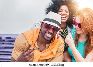 multi racial friends having fun outdoor laughing and enjoying a joke. cheerful young people with carefree happy expressions. concept of diversity and friendship