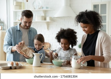 Multi racial full family cooking pastries gathered together in kitchen mixing products fresh ingredients eggs flour and milk make dough preparing holiday cake. Lifestyle, parenthood, cookery concept