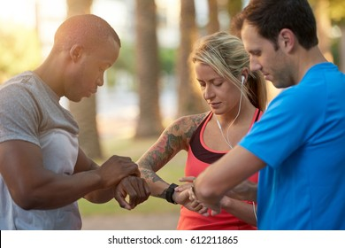 Multi racial group of friends looking at their fitness trackers smartwatch before their run jog workout
