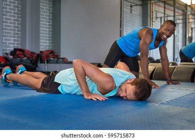 Multi racial gym buddies partners friends resting laughing during their intense workout training