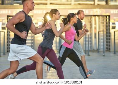 Multi racial team running outdoors on stadium background