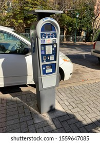 Multi space parking meter on a sidewalk with cars in the background downtown Chattanooga, Tennessee November 13, 2019