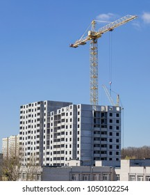 Multi story house from precast concrete panels during construction and building tower crane on background of the sky