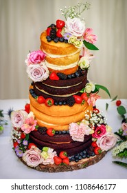 Multi tiered sponge and cream wedding cake decorated with fruit and flowers
