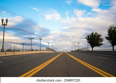 Multiband Wide asphalted road with a dividing strip oncoming traffic, marked by the yellow line, which converge on the horizon on a background of street lights and silhouette of trees along the road.