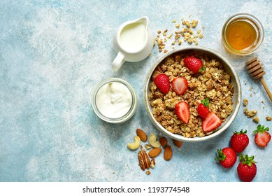 Multicereal homemade organic granola served with fresh strawberry, nuts, honey, milk and yogurt on a light blue slate, stone or concrete background.Top view with copy space.