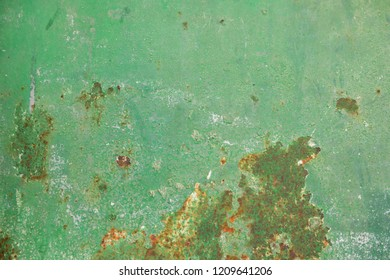Multicolor background: rusty metal surface with green paint that cracks and cracks