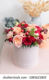 Multicolor bouquet of beautiful flowers on wooden table. Floristry concept. Spring colors. the work of the florist at a flower shop. Vertical photo