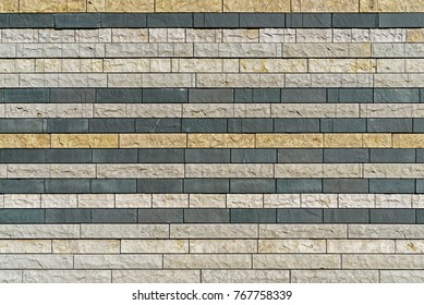 Multicolor brick wall. Rows of blocks. Beige, gray, and tan colors. Rough texture surface.