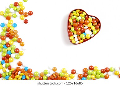 Multicolor candies in heart shape candy box on white background
