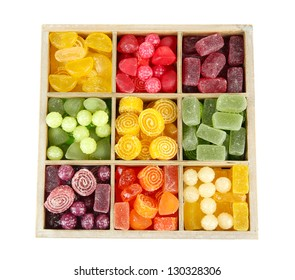 Multicolor candies in wooden box, isolated on white