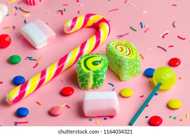 Multicolor, children's, high-calorie, unhealthy candy on a pink background. A table full of sweets.