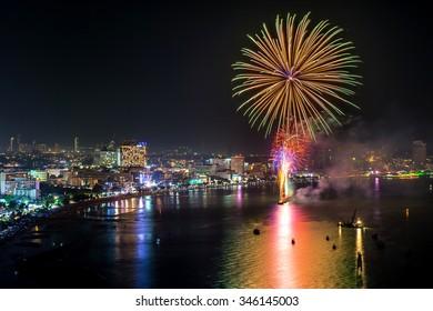 Multicolor fireworks night scene, closeup with pattaya cityscape sea beach view, thailand