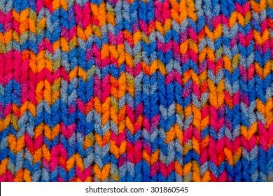 Multicolor front loops of wool boucle yarn knitted background. Fashion knitted background