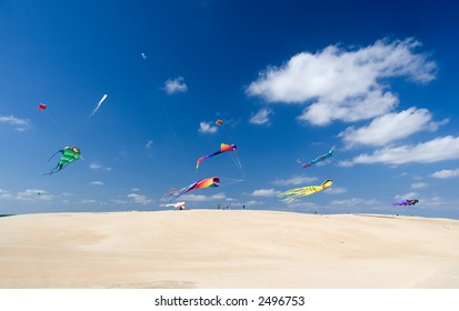 Multicolor kites flying over sandy hill in bright sunny afternoon