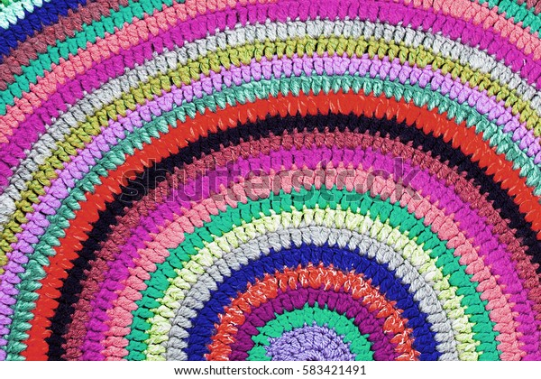 Multicolor knitted round carpet or rug. Close up
