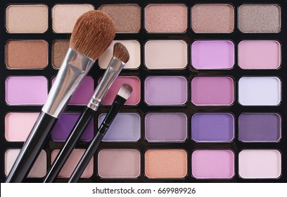 Multicolor palette eyeshadow with brush for make up as sample of cosmetic product on black pallet