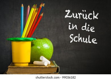 "Multicolor pencils, chalks and green apple on old book against blackboard with text ""Back to school!"" in the German language. School concept"
