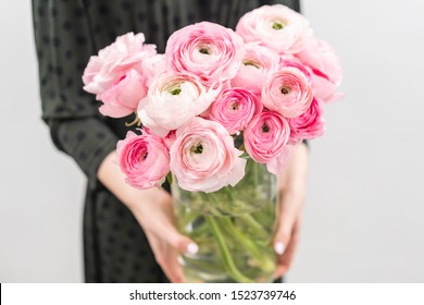 Multicolor pink buttercup, Ranunculus in a vase in woman hand. the work of the florist at a flower shop .