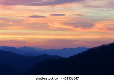 Multicolor sky sunrise above blue ridge mountains.