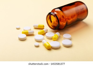 Multicolor tablets and pills capsules from glass bottle on yellow background Heap of assorted various medicine tablets and pills. Health care Close-up Copy space