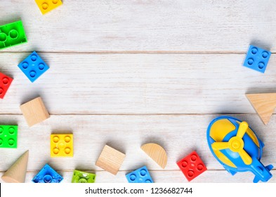 Multicolor toy bricks on white wooden background. Children toys on the table. Flat lay, top view, copy space.