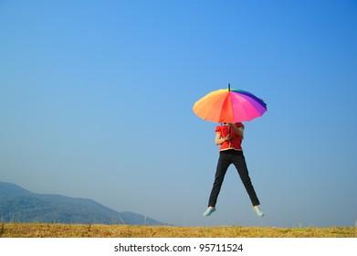 Multicolor umbrella woman jump to Blue sky