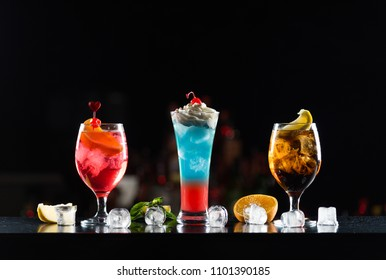 Multi-colored alcoholic cocktails in glasses of different shapes on the bar.