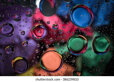 Multi-colored background as seen through water droplets on glass
