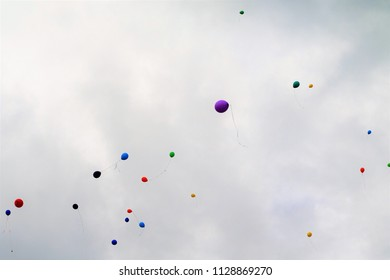 Multicolored balloons against the sky clouds