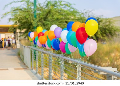 Multicolored balloons at the entrance with blurred people in the background