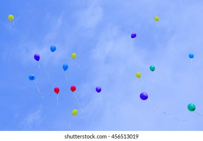 Multicolored balloons flying high in the blue sky