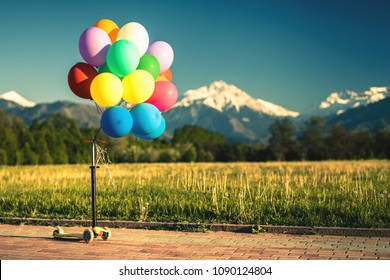 Multicolored balloons with kick scooter outdoor festival on blue sky background with nobody. Special helium balloon for Children Day, Children's Day or Birthday and carnival party