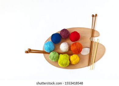 Multi-colored balls of wool yarn for hand knitting and knit needles on wooden palette on white background. The concept of art knitting and creative needlework. Top view, copy space, flat lay, mock up