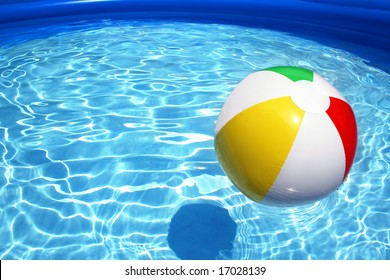 Multicolored beach ball floating on a sparkling blue swimming pool