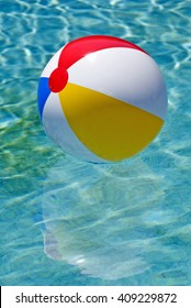 Multicolored beach ball floating in sparkling swimming pool